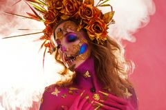 Bright Halloween image, Mexican style with sugar skulls on face. Young beautiful woman bright pink skin royalty free stock photo