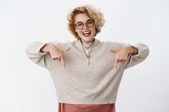Bright and happy friendly-looking charming hipster girlfriend inviting us click or look downwards smiling broadly and royalty free stock photos