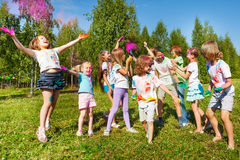 Bright and happy kids playing with colored powder Royalty Free Stock Photos