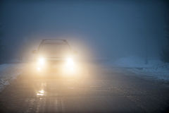 Headlights of car driving in fog. Bright headlights of a car driving on foggy winter road royalty free stock photography