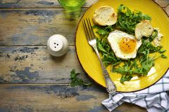 Bright healthy breakfast - mix of salad leaves, fried egg and baguette on a yellow plate over rustic wooden background.Top view stock photography