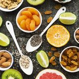 Bright healthy ingredients for proper nutrition: fruits, nuts, berries, superfood, orange, grapefruit, almonds, dried. Apricots, figs dates raisins walnuts chia Royalty Free Stock Photography
