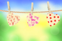 Bright hearts hanging on rope on bright nature background Stock Images