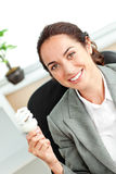 Bright hispanic businesswoman holding a light bulb Stock Image
