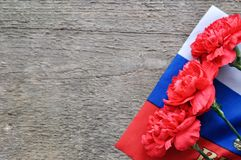 Bright holiday card on February 23. Red carnations and Russian flag on rustic wooden background. Fatherland defender day. The day of military glory royalty free stock photos