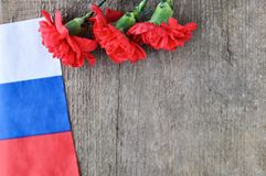 Bright holiday card on February 23. Red carnations and Russian flag on rustic wooden background. Fatherland defender day. The day of military glory royalty free stock image