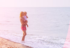 Bright holyday mood. Mother and daughter playing on the beach. Bright holyday mood. Concept of happy family Royalty Free Stock Photo
