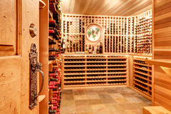 Bright home wine cellar with wooden storage units with bottles. Old antique key lock door know details. Bright home wine cellar with wooden storage units and royalty free stock photos