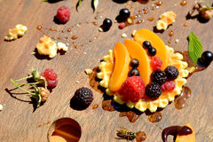 Bright honey, raspberry, currant, peach on crisp waffle closely Royalty Free Stock Images