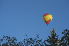 Bright hot air balloon flies in a clear blue sky royalty free stock images
