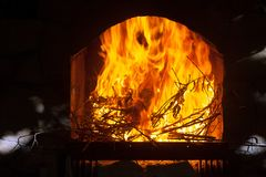A bright and hot flame in the opening of the fireplace. A bright and hot flame, burning branches in the opening of a stone fireplace Royalty Free Stock Photography