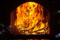 A bright and hot flame in the opening of a stone fireplace. A bright and hot flame, burning branches in the opening of a stone fireplace Stock Photo