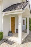 Bright house entry. House entry covered by precipitous roofing based on two linchpins royalty free stock photography