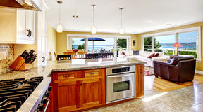 Bright house interior. Living room with walkout deck and kitchen. Area. Wooden cabinets with granite tops ans steel appliances royalty free stock photos