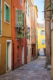 Bright houses on old street in Villefranche-sur-Mer. Row of colourful old buildings with bright window shutters along cobblestone street in medieval town Royalty Free Stock Photography