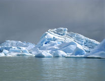 A bright iceberg with dark clouds Stock Photos