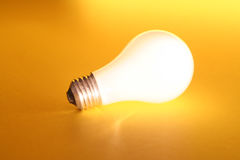 Bright Idea. Bright light bulb on Yellow background Royalty Free Stock Images