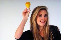 A Bright Idea. Young woman holding aloft a lightbulb royalty free stock photos