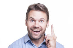 Bright idea. Portrait of handsome bearded Caucasian man holding up one finger and smiling because he has a bright idea on white background Stock Image