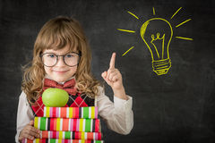 Bright idea. Smart kid in class. Happy child against blackboard. Drawing light bulb idea. Education concept stock photo