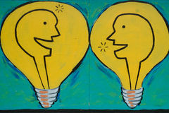 Bright idea. Two light bulbs with silhouette of heads talking or communicating a bright idea stock photo