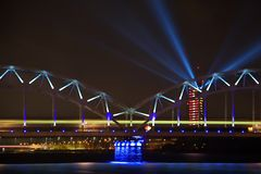 Bright illuminated Railroad Bridge. Latvian Television building bright illuminated in red and white. Blue spot beams projected fro royalty free stock images