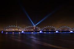 Bright illuminated Railroad Bridge, Riga Radio and TV Tower and Latvian Television building with Blue spot beams projected royalty free stock photos