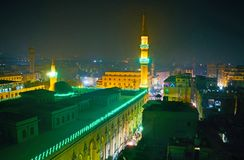 The bright illumination of minaret and walls of Al-Hussain Mosque, surrounded by dark quarters of evening Islamic Cairo district,. Egypt stock photography