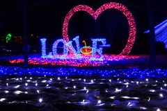 The inscription love and the shape of the heart of the LEDs, which were installed in a city park in Europe, shot at night on the b. Bright inscription love and stock images