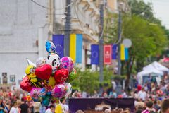 Bright joyful balloons in the air, European flags and people crowd in Soborna Street, Vinnytsia city downtown. Vinnytsia, Ukraine - 18.05.2019: a pile of bright royalty free stock image
