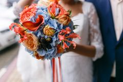Bright and juicy color Wedding bouquet different flowers. Modern bridal bunch with orange tulips, red gloriosa, blue Royalty Free Stock Image