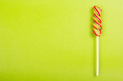 Bright juicy colored lollipop on a green background. Lollipop  in the form of a color spiral. Royalty Free Stock Photo