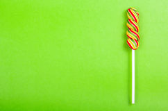 Bright juicy colored lollipop on a green paper background. Lollipop  in the form of a color spiral. Fruit candy. Stock Photo