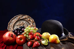 Bright juicy fruit in the classic Dutch still life next to a bowl hat and an old engraved dish.  Stock Photos