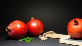 Bright juicy pomegranate fruit and green foliage, black background. Stone kitchen board with wooden handle added on the photo, close-up royalty free stock photos