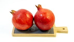 Bright juicy pomegranate fruit, white background, in the photo two fruits. Are placed on a stone kitchen board, close-up royalty free stock photo
