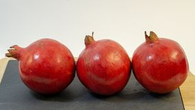 Bright juicy pomegranate fruits, white background, in the photo next three fruits are hardly placed. Fruit is placed on a stone kitchen board, close-up stock images