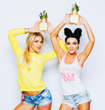 Bright juicy portrait of two cheerful girlfriends, having fun with slice pineapple and smiling. Casual style, bright stock images