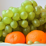 Bright and juicy tangerines, on top a bunch of grapes.  Royalty Free Stock Image