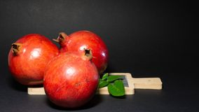 Bright juicy three pomegranate fruits and green foliage, black background. Added to the photo a stone kitchen board with a wooden handle, close-up royalty free stock image