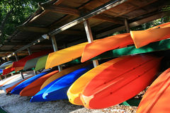 Bright kayaks. Brightly colored kayaks for rent stacked in racks stock photography