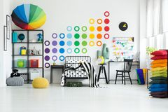 Rainbow dots on white wall. Bright kid`s room with bed, study corner and rainbow dots on white wall stock photography