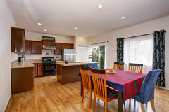 Bright kitchen and dining room interior with colorful curtains and hardwood floor. Stock Photos