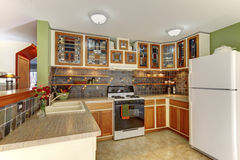 Bright kitchen interior with brown tile and cabinets with staine Stock Images