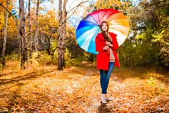 Bright lady in forest. A portrait of a beautiful young woman in an autumn forest with bright and colorful umbrella. Lifestyle, autumn fashion, beauty stock image