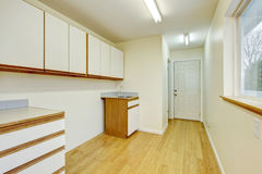 Bright laundry room interior with cabinets and hardwood flooring. Stock Images