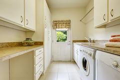 Bright laundry room with white cabinets Stock Image