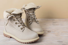 Bright leather winter boots on a light wooden background. Stock Photography