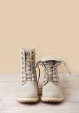 Bright leather winter boots on a light wooden background. Stock Photos