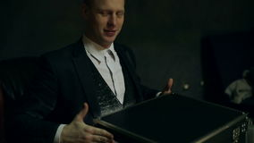 Bright light appearing from the box, and falling on the face of the illusionist. stock video